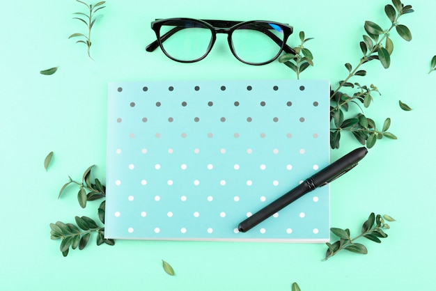 Blauw notitieboekje in een cirkel met een potlood, glazen, groene bladeren