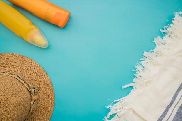 Blauw oppervlak met handdoek, hoed en lotions