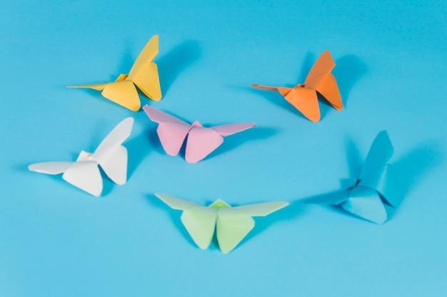 Blauw oppervlak met papieren vlinders