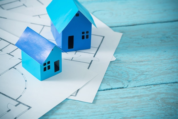 Blauw papier huizen op oude houten tafel