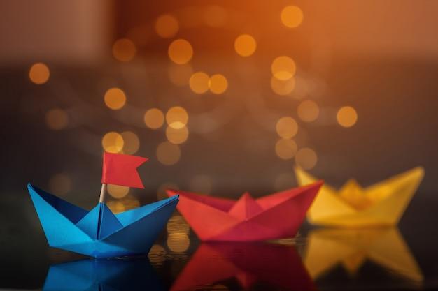 Blauw papieren schip met vlag onder andere schepen.
