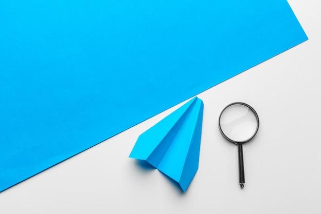 Blauw papieren vliegtuig en vergrootglas