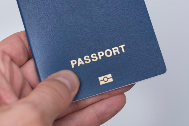 Blauw paspoort met biometrische gegevens in de hand van een man.