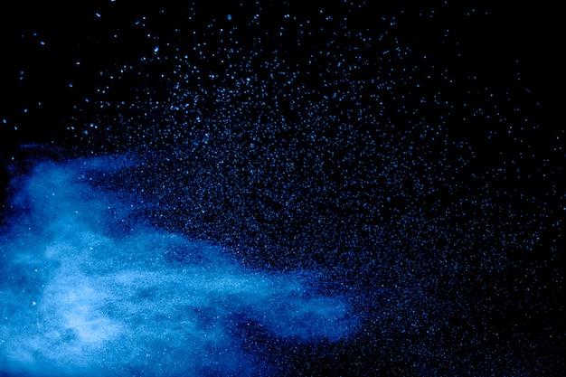 Blauw poeder exploderen wolk op zwart oppervlak. gelanceerde blauwe stofdeeltjes spatten op de achtergrond.
