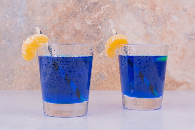 Blauw sap in glazen met plakjes mandarijn.