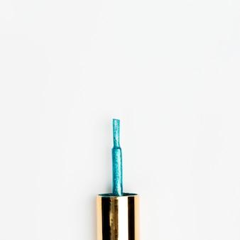 Blauw schitter nagellakborstel die op witte achtergrond wordt geïsoleerd