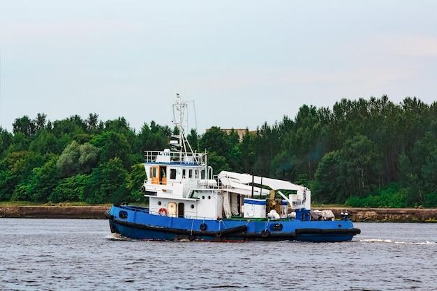 Blauw sleepschip dat naar de vrachtterminal verhuist. industriële dienstverlening