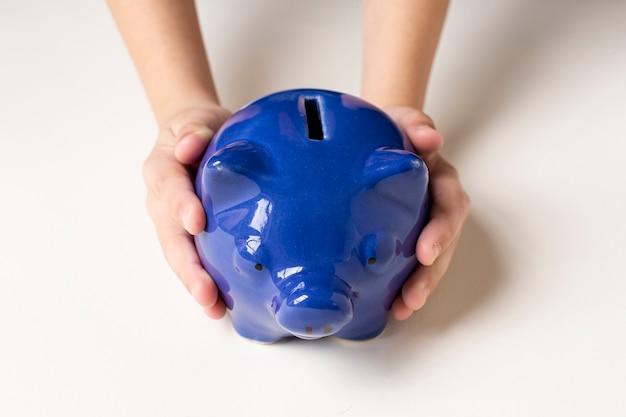 Blauw spaarvarken dat in handen wordt gehouden