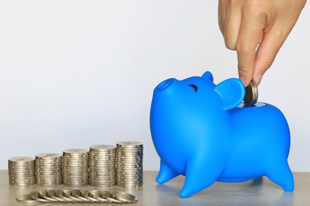 Blauw spaarvarken en gestapelde munten