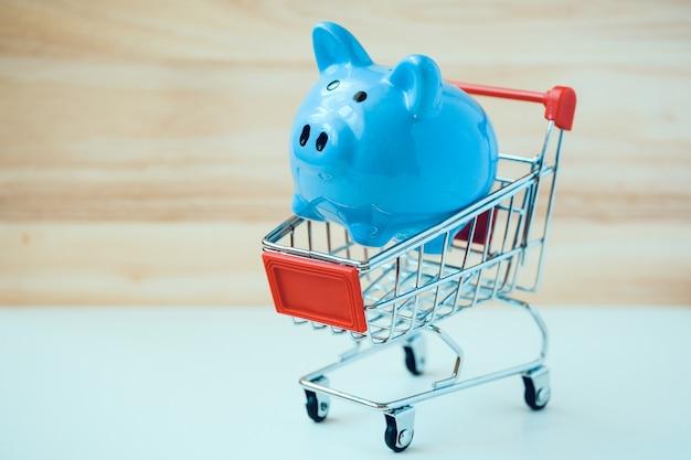 Blauw spaarvarken in klein stuk speelgoed boodschappenwagentje