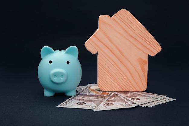 Blauw spaarvarken met model van huis en geldbankbiljetten op blauwe achtergrond. spaargeld voor huis kopen