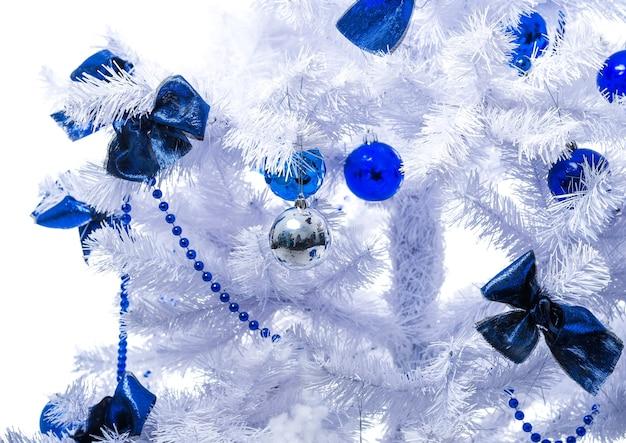 Blauw speelgoed hangt aan een witte kerstboom.