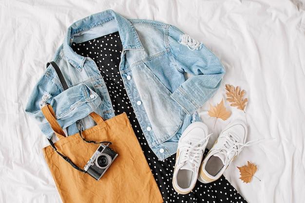 Blauw spijkerjack en zwarte jurk, sneakers met draagtas en fotocamera op wit bed. stijlvolle herfst- of lente-outfit voor dames. trendy kleding. plat lag, bovenaanzicht.
