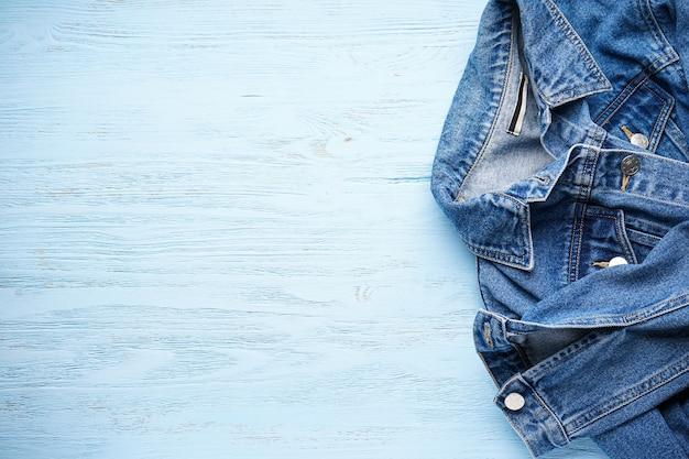 Blauw spijkerjasje op lichtblauwe houten tafel, ruimte voor tekst. plat leggen.