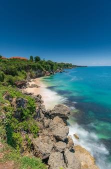 Blauw strand met rotsen en huizen aan de kust met kopie ruimte voor tekst