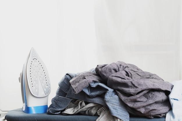 Blauw strijkijzer en kleding op de strijkplank geplaatst.