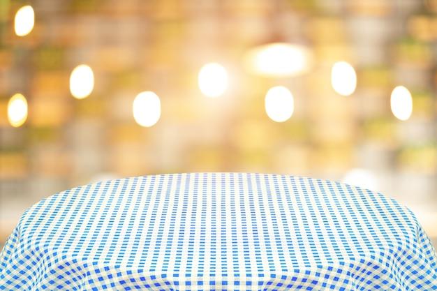 Blauw tafelkleed met onscherpe achtergrond van het restaurant. achtergrond voor platte tekst of producten