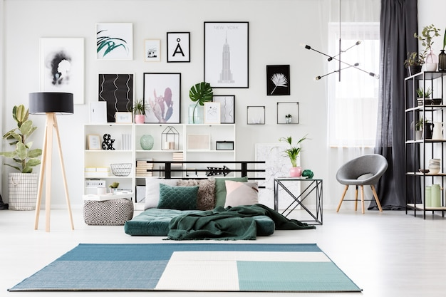 Blauw tapijt in de buurt van groene matras en lamp in ruim slaapkamerinterieur met fauteuil en galerij