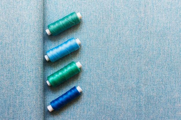 Blauw textielweefsel met vier groenachtig blauwe naaigaren