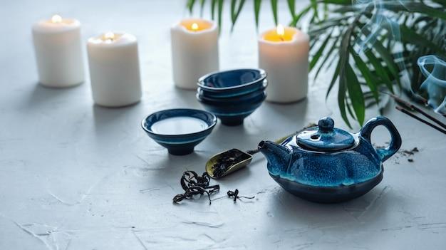 Blauw theeservies voor chinese theeceremonie. brandende kaarsen en geparfumeerde koppels.