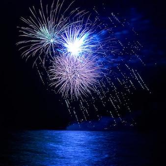 Blauw vakantievuurwerk boven het meer met waterreflectie en zwarte lucht