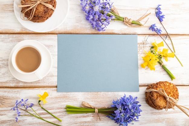 Blauw vel papier met havermoutkoekjes lentebloemen boshyacinten narcissen en kopje koffie