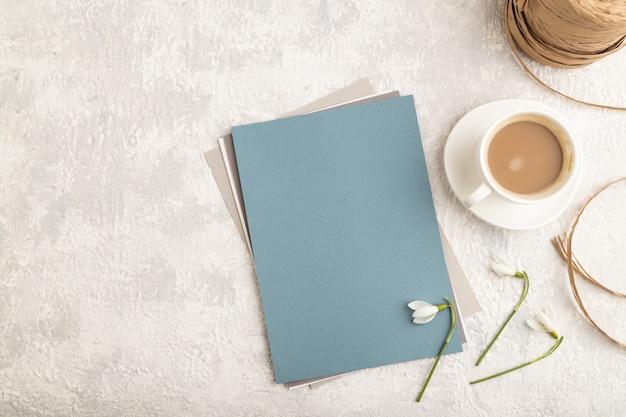 Blauw vel papier met sneeuwklokje galanthus bloemen en kopje koffie
