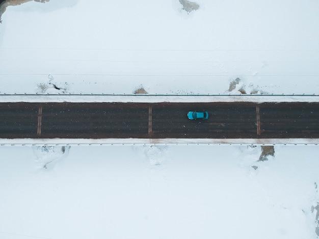 Blauw voertuig op weg in de winter