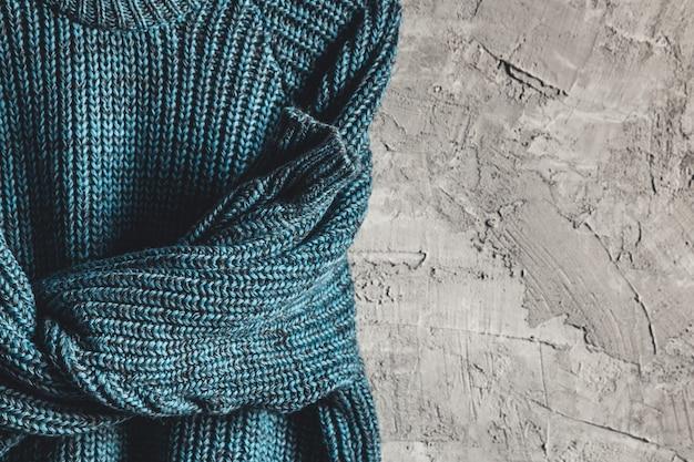 Blauw warm shirt met lange mouwen op zwarte hanger hang op een grijze achtergrond