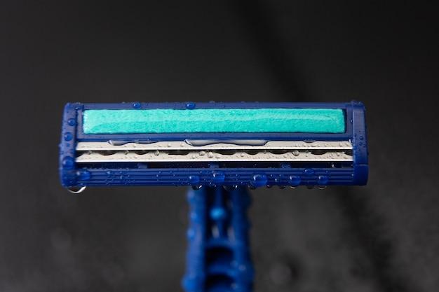 Blauw wegwerpscheermesje met waterdruppels