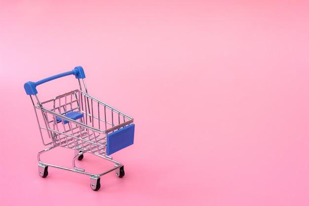 Blauw winkelwagentje op roze