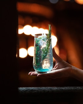 Blauw witte alcoholdrank met een tak van rozemarijn in de hand.