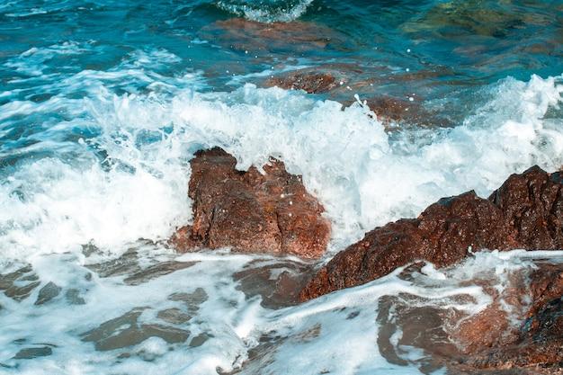 Blauw zeegezicht met golven en rotsen