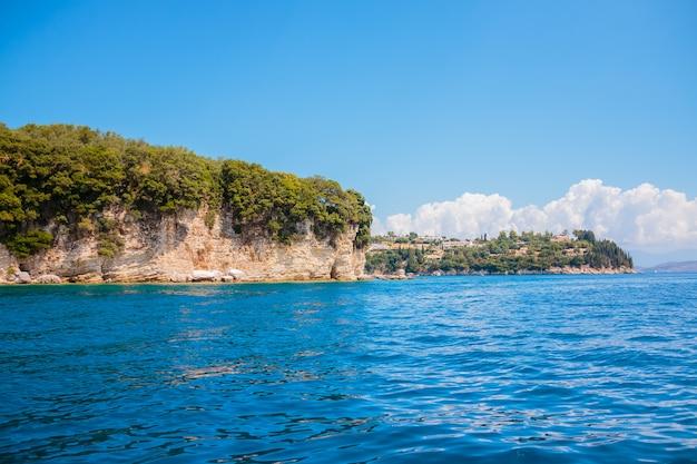 Blauw zeewater en bergen. heldere blauwe hemel zonder wolken en skyline van de berg. zee cruise concept.