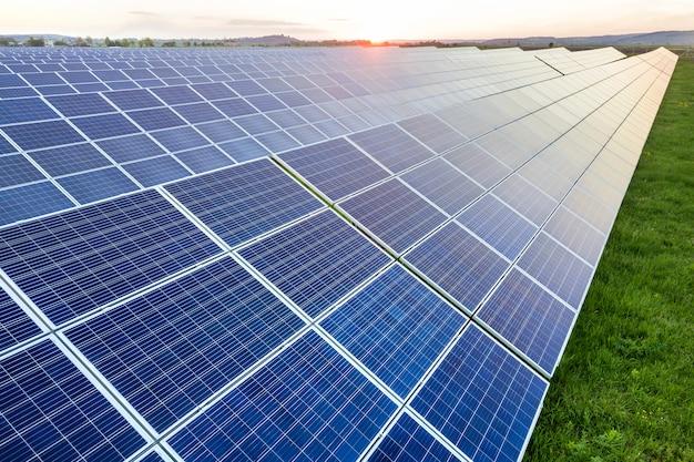 Blauw zonnesysteem van foto voltaic panelen die duurzame schone energie op landelijk landschap produceren en zonachtergrond plaatsen.