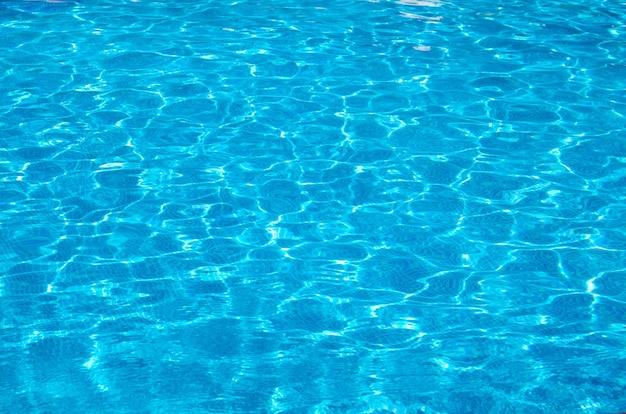 Blauw zwembadwater met reflecties van de zon