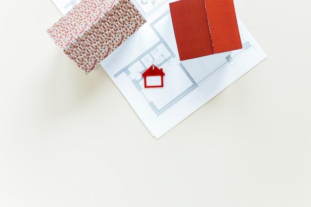 Blauwdruk en huismodel met sleutelhanger op witte achtergrond wordt geïsoleerd die