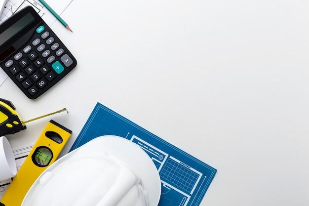 Blauwdruk met constructor hoed en rekenmachine