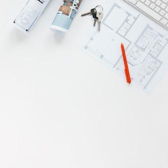 Blauwdruk met sleutels en rode pen die op witte achtergrond wordt geïsoleerd