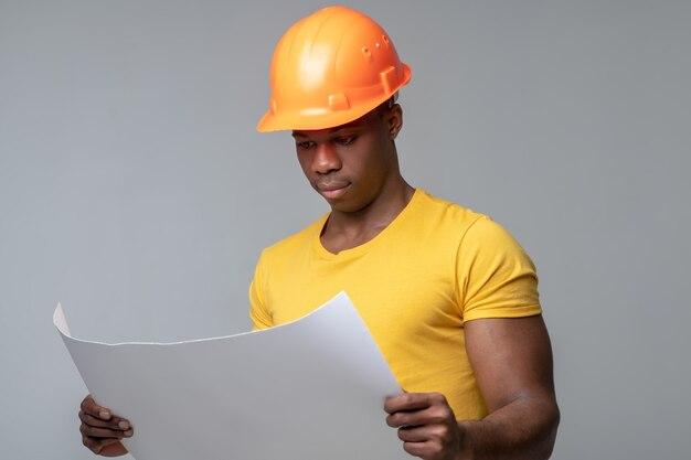 Blauwdruk tekening. ernstige attente donkere jonge man in helm overweegt blauwdruk tekening in handen te houden
