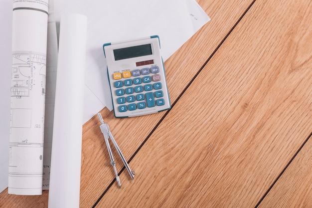 Blauwdrukken in de buurt van rekenmachine en kompassen