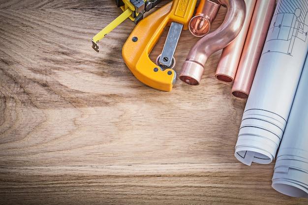 Blauwdrukken meetlint waterpijp snijder fittingen op houten plank sanitair concept