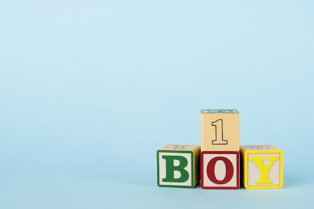Blauwe achtergrond met gekleurde kubussen met letters boy en nummer