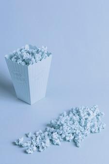 Blauwe achtergrond met isometrische popcorn