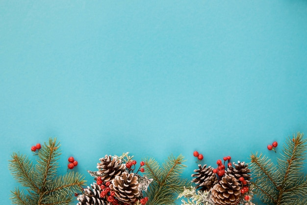 Blauwe achtergrond met pijnboombladeren en kegels
