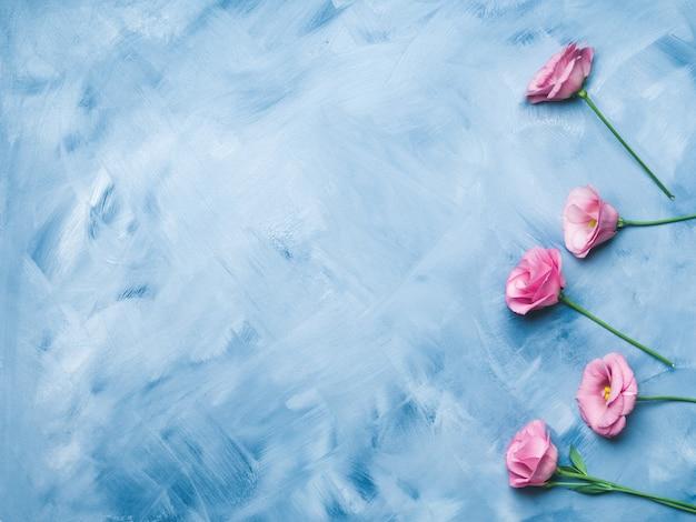Blauwe achtergrond met roze bloemen
