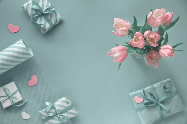 Blauwe achtergrond met roze tulpen, gestreept inpakpapier en geschenkdozen