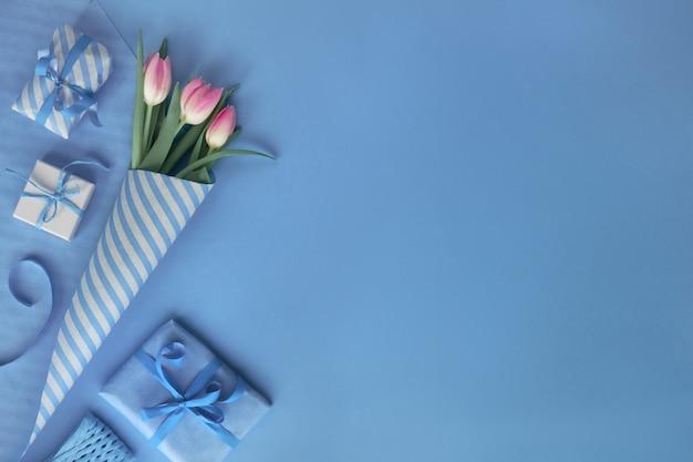 Blauwe achtergrond met roze tulpen, hyacint, inpakpapier en geschenkdozen
