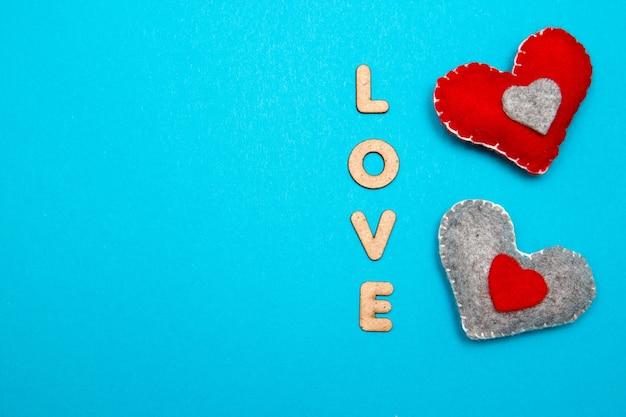 Blauwe achtergrond met twee rood hart en liefdewoord