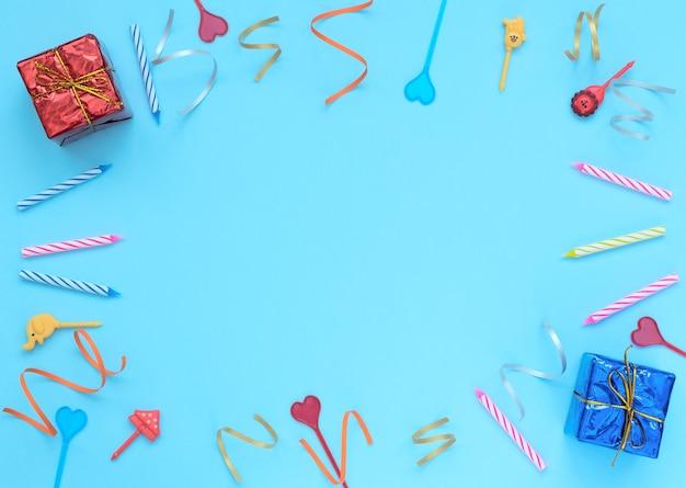 Blauwe achtergrond met verpakte geschenkdozen, slingers, kaarsen en spiesjes. verjaardag, feestconcept.